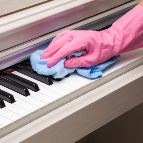 person cleaning piano keys
